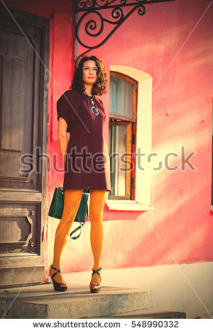 stock-photo-beautiful-smiling-middle-aged-woman-in-a-burgundy-dress-and-green-hand-bag-on-the-porch-of-an-old-548990332